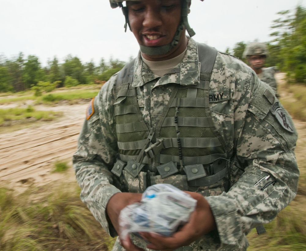 Spc. Demaricus Rowley, a finance specialist with Headquarters and Headquarters Company, U.S Army Civil Affairs & Psychological Operations Command (Airborne), handles money prior to an exercise that brought together Soldiers from USACAPOC(A) and the 169th Aviation Regiment at Fort Bragg, N.C., June 27, 2015. The Soldiers rode a UH-60 Black Hawk helicopter to the training site where they were then asked to negotiate with local civilians.  Rowley is a security officer at Fort Bragg. (U.S. Army photo by Sgt. Felix R. Fimbres, USACAPOC(A) PAO)