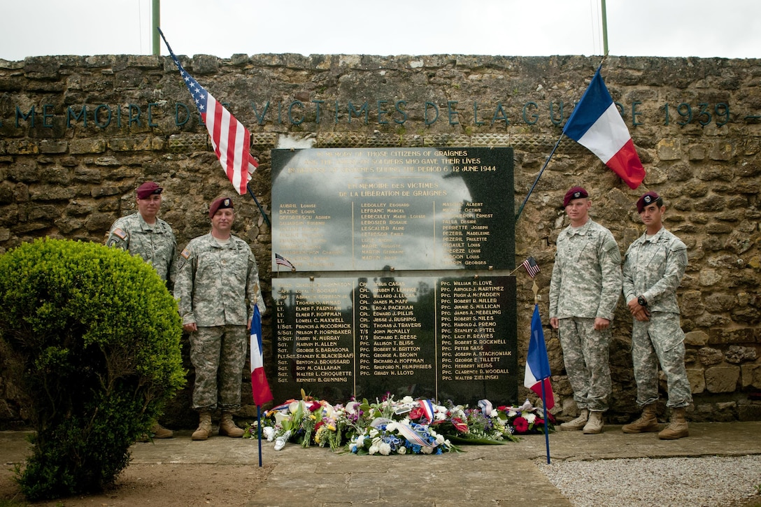 Soldiers assigned to the historic 507th Parachute Infantry Regiment pose for a picture after a ceremony. The worst misdrop on D-Day happened to the Soldiers of the 3rd Battalion, 507th Parachute Infantry Regiment. They were to be dropped near Amfreville, France, but ended up 18 miles southeast, in a town called Graignes. Behind enemy lines and unsure of the situation, the leadership made a decision to stay were they were and defend that land. As luck would have it, the 170 Soldiers and 10 Officers landed in the mayor's field. A town meeting was held and all decided they would rally with the Soldiers and provide support in the form of food, water, shelter and even their own lives for the defense of their town against the Germans. On June 5, 2015, service members with Joint Task Force D-Day 71 took part in a ceremony in Graignes, France, to honor the lives of all lost during the battle that waged here June 6-12, 1944. The 507th PIR was represented, as well as the U.S. Army Civil Affairs and Psychological Operations Command (Airborne), Commander, Naval Forces Europe, and the Dutch Army and Band.  Over 380 service members from Europe and affiliated D-Day historical units are participating in the 71st anniversary as part of JTF D-Day 71. The Task Force, based in Saint Mere Eglise, France, is supporting local events across Normandy, from  June 2-8, 2015 to commemorate the selfless actions by all the allies on D-Day that continue to resonate 71 years later. (U.S. Army photo by Capt. Saska Ball, USACAPOC(A) PAO)