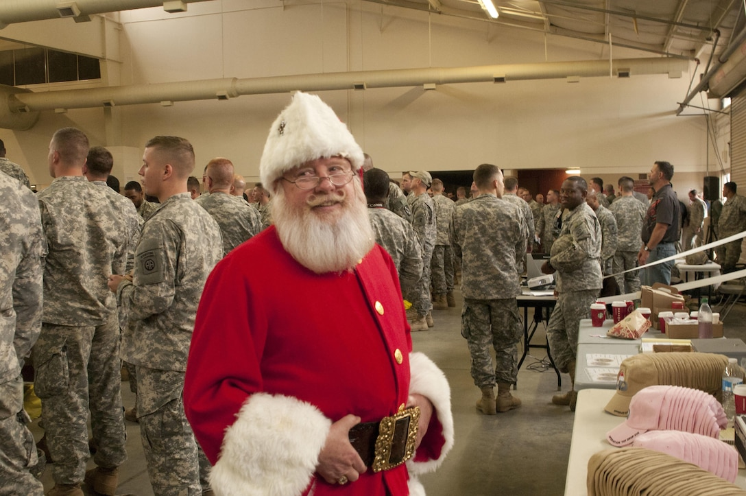 Santa Claus himself spends time with paratroopers who wait patiently, hoping their ticket number will be called for an opportunity to earn foreign jump wings at the 17th Annual Randy Oler Memorial Operation Toy Drop, hosted by U.S. Army Civil Affairs and Psychological Operations Command (Airborne), Dec. 5, 2014, at Pope Field, North Carolina. Operation Toy Drop is the world's largest combined airborne operation with seven allied partner nation paratroopers participating and allows Soldiers the opportunity to help children in need everywhere receive toys for the holidays. (U.S. Army photo by Spc. Kimber Gillus)