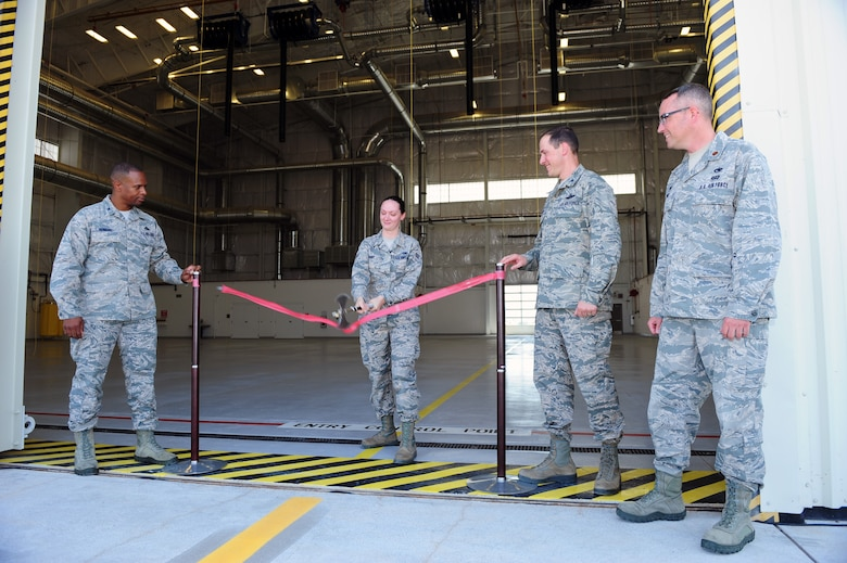 U.S. Air Force Airman 1st Class Desaray Grant, 355th Component Maintenance Squadron aircraft fuel systems apprentice, slashes through a ribbon signifying the activation of the 355th CMS's new Joint fuel cell repair hangar at Davis-Monthan Air Force Base, Ariz., July 13, 2015. The hangar is Air Combat Command's largest aircraft fuel systems repair section. (U.S. Air Force photo by Airman 1st Class Chris Drzazgowski/Released)