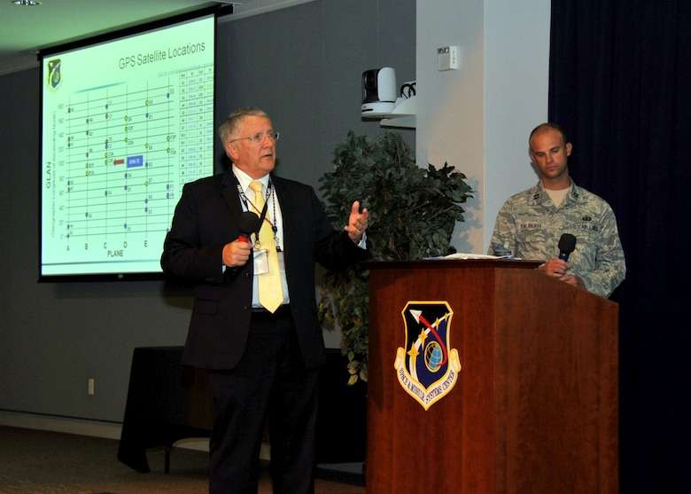 """R. Bruce Lagatree, GPS System Engineering and Integration Program principal systems engineer for Leidos, previously known as Science Applications International Corporation and Capt. Nick Laliberte, Government Mission Integration Manager from the Space and Missile Systems Center's Launch Systems Directorate provides a pre-launch briefing to an audience of more than 150 SMC personnel in the Gordon Conference Center at Los Angeles Air Force Base in El Segundo, Calif. On July 15, 2015, a United Launch Alliance Atlas V in the """"401"""" vehicle configuration of a four-meter-wide payload fairing, zero solid rocket boosters and a single engine upper stage successfully carried a GPS IIF-10 satellite into orbit at 11:36 a.m. EDT from Launch Complex 41 at Cape Canaveral Air Force Station in Florida for the Global Positioning System navigation network. (U.S. Air Force photo/Sarah Corrice)"""