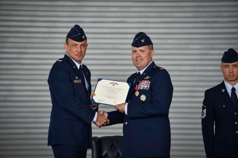Colonel John Lamontagne (left), 437th Airlift Wing commander, presents a Legion of Merit to Col. Fred Boehm July 15, 2015, during the 437th Operations Group change of command at Joint Base Charleston, S.C. Boehm has served as the 437th OG commander since July 2013. Following the change of command, Boehm's next assignment will take him to Saudi Arabia where he will be the chief of the Joint Advisory Division for Saudi Arabia. (U.S. Air Force photo/Senior Airman Jared Trimarchi)