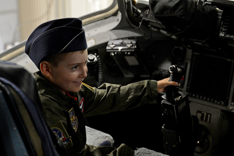 Ewan McFadgen, Pilot for a Day, sits in the pilot seat of a C-17 Globemaster III July 10, 2015, during his tour of Joint Base Lewis-McChord, Wash. McFadgen and his family explored the aircraft before concluding their tour with a C-17 flight simulator. (U.S. Air Force photo/Airman 1st Class Keoni Chavarria)