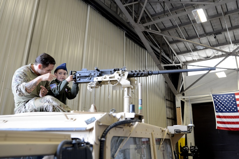 Ewan McFadgen, Pilot for a Day, sits in a turret of an armored Humvee with a combat controller at the 22nd Special Tactics Squadron, July 10, 2015, during his tour of Joint Base Lewis-McChord, Wash. While at the 22nd STS, McFadgen visited the air traffic control simulator and was able to listen to the commands over the radio. (U.S. Air Force photo/Airman 1st Class Keoni Chavarria)