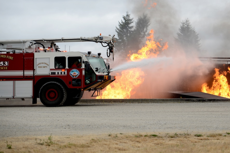Ewan McFadgen, Pilot for a Day, controls the water hose in a McChord Field fire truck to put out a controlled fire July 10, 2015, during his tour of Joint Base Lewis-McChord, Wash. The Pilot for a Day program gives children affected with a catastrophic illness, on their way to recovery, a tour of JBLM. (U.S. Air Force photo/Airman 1st Class Keoni Chavarria)
