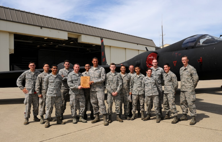"""Airmen from the 9th Aircraft Maintenance Squadron pose with a U-2 Dragon Lady at Beale Air Force Base, California, July 14, 2015. The Airmen were recognized for a """"black-letter jet,"""" a rare accomplishment in which a plane is flown with zero discrepancies. The achievement has not happened in 13 years at Beale. (U.S. Air Force photo by Airman Preston L. Cherry)"""
