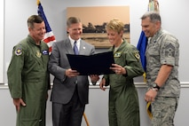 """Louisiana State Senator Barrow Peacock and 2nd Bomb Wing leadership read a resolution at Barksdale Air Force Base, La., July 13, 2015. The resolution congratulates the 2nd BW for earning the 2014 Brigadier General Frederick W. Castle Award as Air Force Global Strike Command's best bomb wing of the year. Throughout 2014, the 2nd BW reformed processes which earned Air Force and Department of Defense accolades punctuated by the highest possible ratings on multiple major inspections. This is the second time 2nd BW has earned the prestigious award, the first being in 2010. """"Whether it is their role in the Nuclear Enterprise, supporting combatant commanders or enhancing the capabilities of their base, the Airmen of Barksdale, in conjunction with community partners, are making a difference every day,"""" the resolution reads. (U.S. Air Force photo/Airman 1st Class Curt Beach)"""