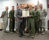 """Louisiana State Senator Barrow Peacock presents Col. Kristin Goodwin, 2nd Bomb Wing commander, and 2nd BW leadership with a resolution at Barksdale Air Force Base, La., July 13, 2015. The resolution, written by Peacock, congratulates the 2nd BW for earning the 2014 Brigadier General Frederick W. Castle Award as Air Force Global Strike Command's best bomb wing of the year. Throughout 2014, 2nd BW reformed processes which earned Air Force and Department of Defense accolades punctuated by the highest possible ratings on multiple major inspections. """"Whether it is their role in the Nuclear Enterprise, supporting combatant commanders or enhancing the capabilities of their base, the Airmen of Barksdale, in conjunction with community partners, are making a difference every day,"""" the resolution reads. (U.S. Air Force photo/Airman 1st Class Curt Beach)"""