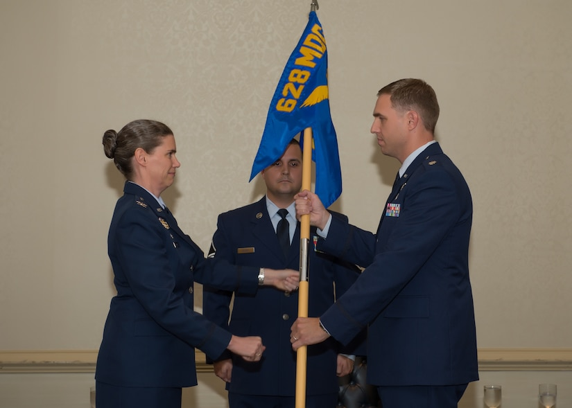 Colonel Margret Jones, 628th Medical Group commander passes the guidon to Lt. Col. Brian Neese, the new 628th Medical Operations Squadron commander during a change of command ceremony July 7, 2015 at Joint Base Charleston, S.C. Neese comes to JB Charleston from Davis Monthan Air Force Base, Az., where he was the chief of  the International Health Specialist Division, Command Surgeon Directorate for the 12th Air Force and Air Forces Southern. The outgoing 628th MDOS commander, Lt. Col. Luis Otero is headed to Maxwell Air Force Base, Al., where he will attend Air War College. (Courtesy Photo)