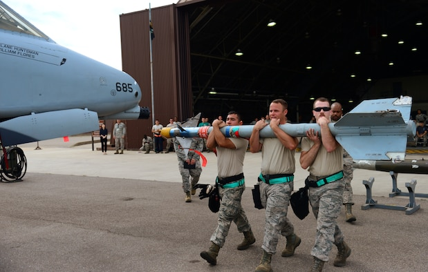 The U.S. Air Force 25th Aircraft Maintenance Unit load team carries an air-to-air missile to their A-10 Thunderbolt II during the quarterly weapons load competition at Osan Air Base, Republic of Korea, July 10, 2015. The event adds an element of competition to a qualification test for the technicians; competitors must complete a written test and a practical demonstration of skill within a fixed amount of time in order to maintain mission readiness status. (U.S. Air Force photo by Staff Sgt. Amber Grimm/Released)