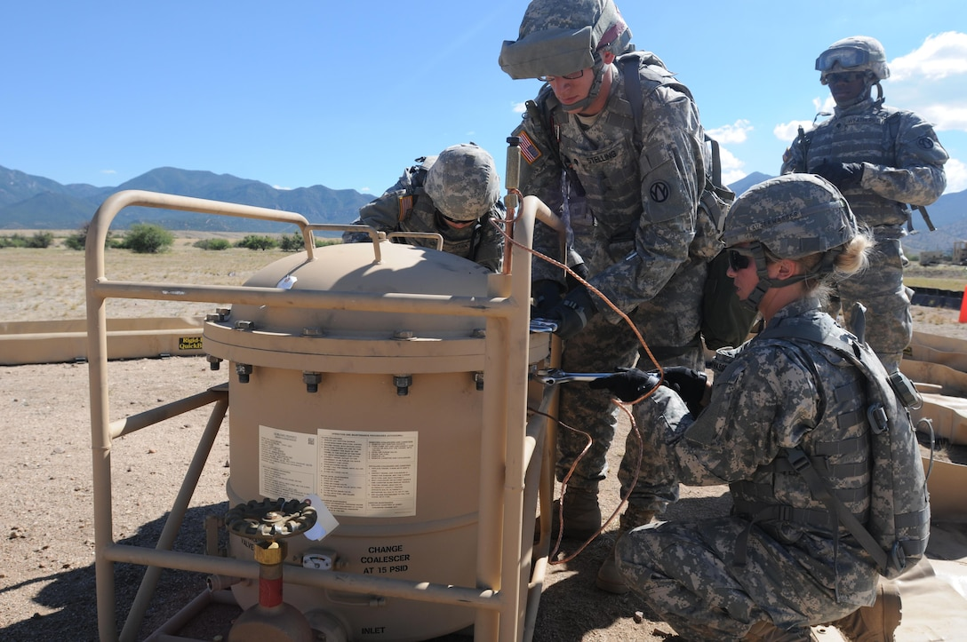 """U.S. Army Reserve Sgt. Vanessa Lauterwasser, Spc. Melissa Stark and Spc. Tyler Stelling work to remove the lid of a filter separator tank during the Quartermaster Liquid Logistics Exercise (QLLEX) on Fort Huachuca, Ariz., June 10, 2015. The three soldiers are petroleum supply specialists assigned to the 383rd Quartermaster Company from St. Charles, Mo. The unit is tasked with running the """"bag farm,"""" where fuel is stored during the QLLEX. (U.S. Army Reserve photo by Capt. Jill O'Dell, 364th Press Camp Headquarters)"""