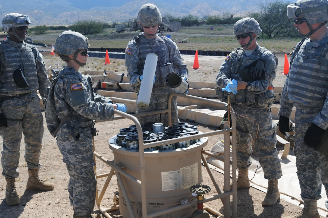 """U.S. Army Reserve Sgt. Ryan Giegling inspect the filters in the filter separator tank during the Quartermaster Liquid Logistics Exercise (QLLEX) on Fort Huachuca, Ariz., June 10, 2015. According to Sgt. Vanessa Lauterwasser, clean rubber gloves must be worn while touching the filters to prevent any contamination in the fuel. Both Giegling and Lauterwasser are petroleum supply specialists assigned to the 383rd Quartermaster Company from St. Charles, Mo. The unit is tasked with running the """"bag farm,"""" where fuel is stored during the QLLEX. (U.S. Army Reserve photo by Capt. Jill O'Dell, 364th Press Camp Headquarters)"""