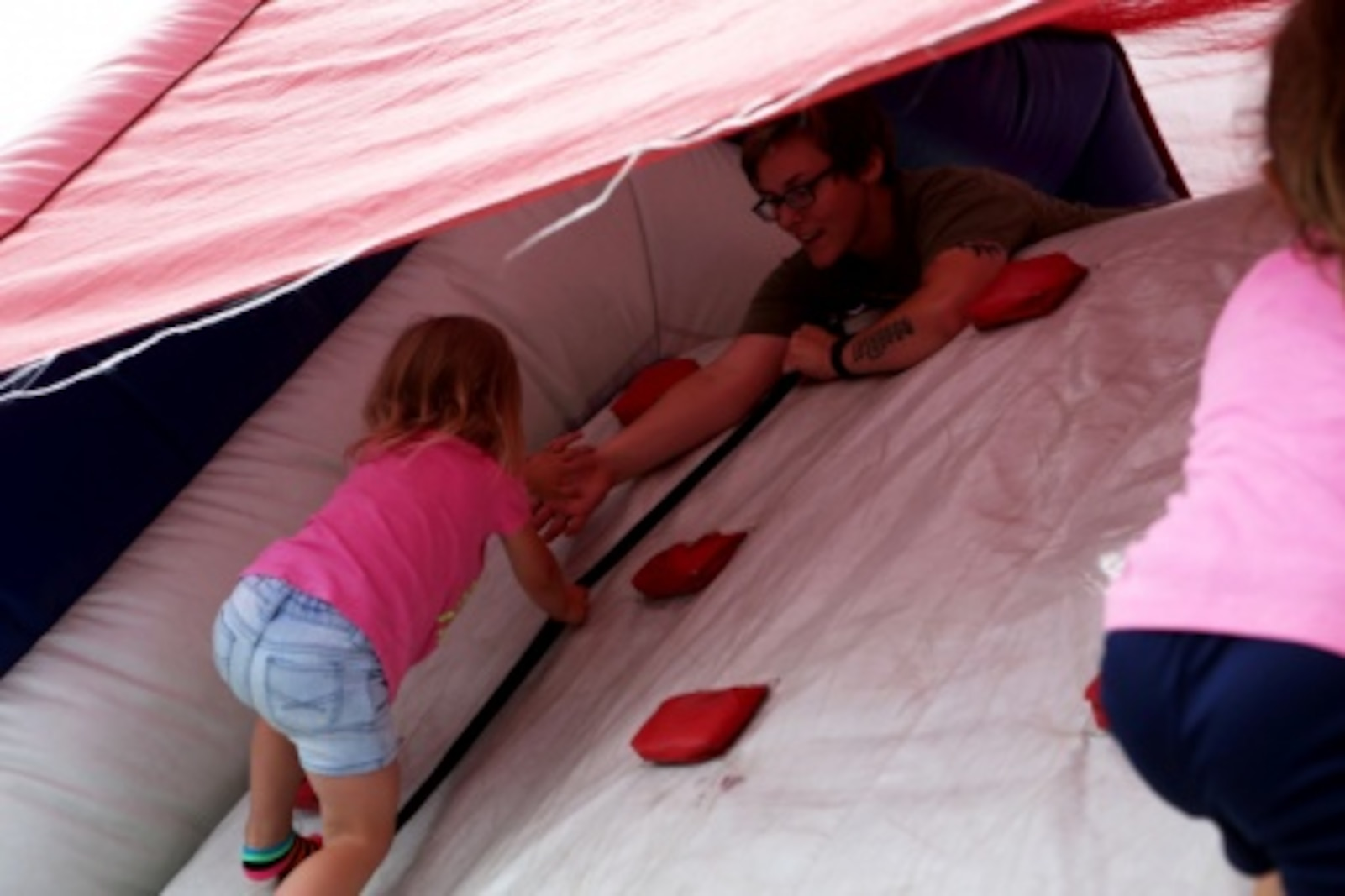 Sergeant Chantelle Imhoff, 7th Engineer Support Battalion, 1st Marine Logistics Group, helps her daughter, Addison, climb a bouncy house rope ladder at a family day celebration for Marines and Sailors of 7th ESB aboard Camp Pendleton, Calif., July 10, 2015. Included in the celebration were bouncy houses and displays that allowed them to look at things like sniper rifles, armored vehicles and Explosive Ordnance Disposal gear.