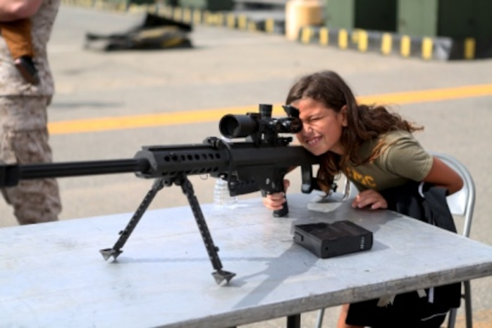 Haliyah, the daughter of Staff Sgt. Henry Hernandez, looks through the scope on a .50 caliber Special Application Scoped Rifle at a family day held by 7th Engineer Support Battalion, 1st Marine Logistics Group, aboard Camp Pendleton, Calif., July 10, 2015. Included in the celebration were bouncy houses and displays that allowed them to look at things like sniper rifles, armored vehicles and Explosive Ordnance Disposal gear.