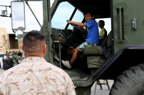 Sergeant Michael Obado, heavy equipment floor chief, 7th Engineer Support Battalion, 1st Marine Logistics Group, watches as his little boy, Nozo, explores an armored truck at a family day celebration for Marines and Sailors of 7th ESB aboard Camp Pendleton, Calif., July 10, 2015. Included in the celebration were bouncy houses and displays that allowed them to look at things like sniper rifles, armored vehicles and Explosive Ordnance Disposal gear.