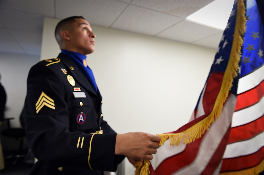 Sgt. Angel Olivo, assigned to the Chicago based 85th Support Command, prepares a U.S. flag before a presentation of colors at the Chicago Cubs vs Miami Marlins game at Wrigley Field with more than 41,000 in attendance, July 3. The game was one of three games, during the Fourth of July weekend, for soldiers participating from the local unit. (U.S. Army photo by Sgt. 1st Class Anthony L. Taylor/Released)