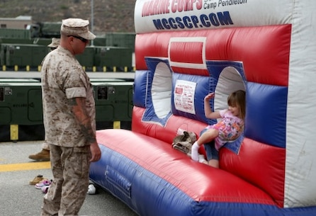 Gunnery Sgt. Jeremy Thrane, platoon sergeant, 7th Engineer Support Battalion, 1st Marine Logistics Group, gets called into a bouncy house by his daughter, Elleanna, at a family day celebration for Marines and Sailors of 7th ESB aboard Camp Pendleton, Calif., July 10, 2015. Included in the celebration were bouncy houses and displays that allowed them to look at things like sniper rifles, armored vehicles and Explosive Ordnance Disposal gear.