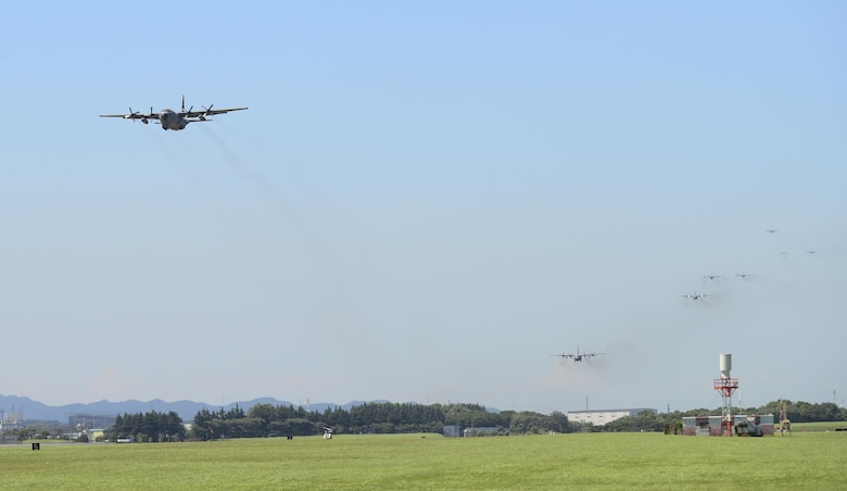 Multiple U.S. Air Force C-130 Hercules aircraft fly over the airfield during a training exercise, Yokota Air Base, Japan, July 14, 2015.. Ten C-130s participated in the exercise which tested the 36th Airlift Squadron's ability to perform large formation flights. (U.S. Air Force photo by Senior Airman David Owsianka/Released)