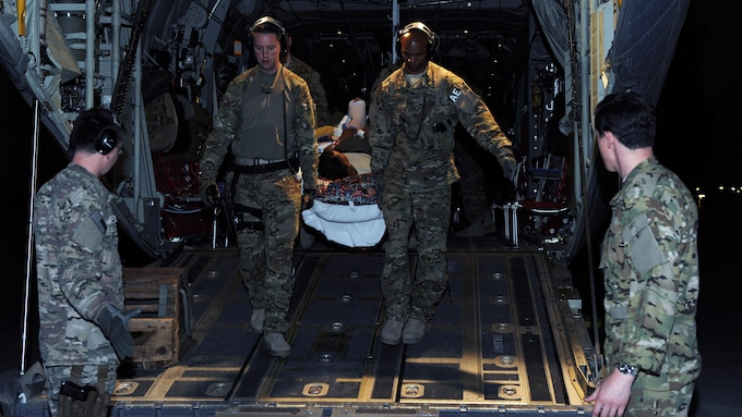 U.S. Air Force Tech. Sgt. Alexander Finn and Tech. Sgt. Johnny Busby, 455th Expeditionary Aeromedical Evacuation Squadron technicians, transport a patient from a C-130 Hercules to an ambulance in Southwest Asia, April 19, 2015. (U.S. Air Force photo by Staff Sgt. Whitney Amstutz)