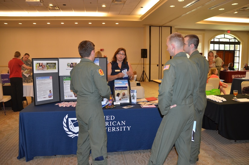 A group of Airmen speak with Penny Davila, the military Education coordinator for Allied American University July 16, 2015 during an education fair held at the club on Joint Base Charleston, S.C. The University of South Carolina, Kaplan University, Embry Riddle, Charleston Southern University and Full Sail University were five of 40 schools that were on hand to speak with members of the JB Charleston community about continued education. The VA was also on hand to answer any Montgomery GI Bill or Post 9-11 questions. (U.S. Air Force photo / Trisha Gallaway)