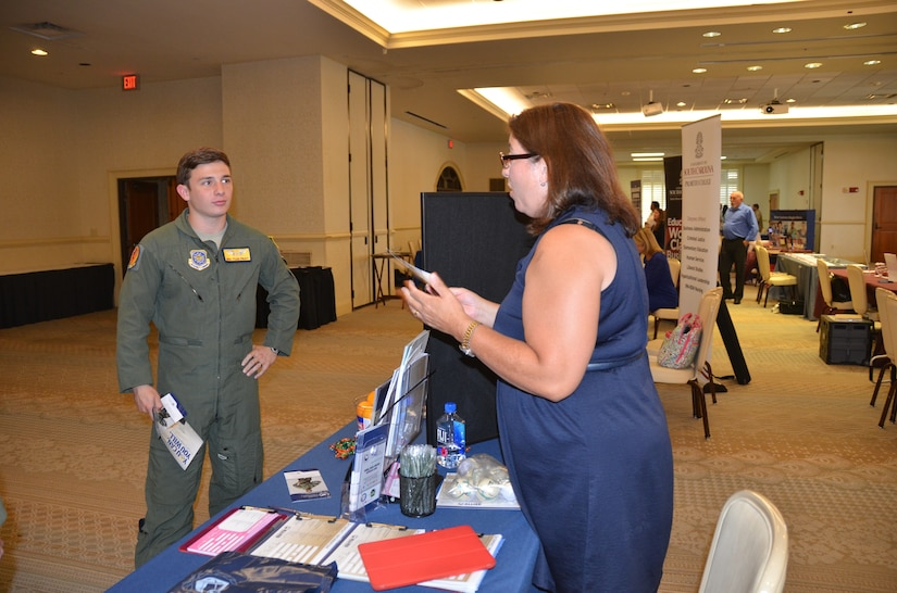 Senior Airman Tyler Pruitt, 16th Airlift Squadron loadmaster speaks with Penny Davila, the military Education coordinator for Allied American University July 16, 2015 during an education fair held at the club on Joint Base Charleston, S.C. The University of South Carolina, Kaplan University, Embry Riddle, Charleston Southern University and Full Sail University were five of 40 schools that were on hand to speak with members of the JB Charleston community about continued education. The VA was also on hand to answer any Montgomery GI Bill or Post 9-11 questions. (U.S. Air Force photo / Trisha Gallaway)