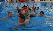 Members of the 39th Civil Engineer Squadron Explosive Ordnance Disposal team swim with their boat to shore after capsizing during the 2nd Annual Cardboard Cup Race July 10, 2015, at Incirlik Air Base, Turkey. Units from across the base designed, built and raced boats made from cardboard and duct tape. (U.S. Air Force photo by Senior Airman Michael Battles/Released)