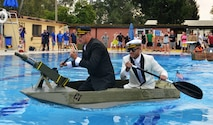 Two Airmen from Team Incirlik paddle across the base pool during the 2nd Annual Cardboard Cup Race July 10, 2015, at Incirlik Air Base, Turkey. Units from across the base designed, built and raced boats made from cardboard and duct tape. (U.S. Air Force photo by Senior Airman Michael Battles/Released)