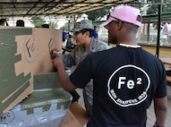 Maj. Eusebia Rios, 39th Air Base Wing deputy chaplain, decorates the FE2 cardboard boat during the 2nd Annual Cardboard Cup Race July 10, 2015, at Incirlik Air Base, Turkey. Units from across the base designed, built and raced boats made from cardboard and duct tape. (U.S. Air Force photo by Senior Airman Michael Battles/Released)