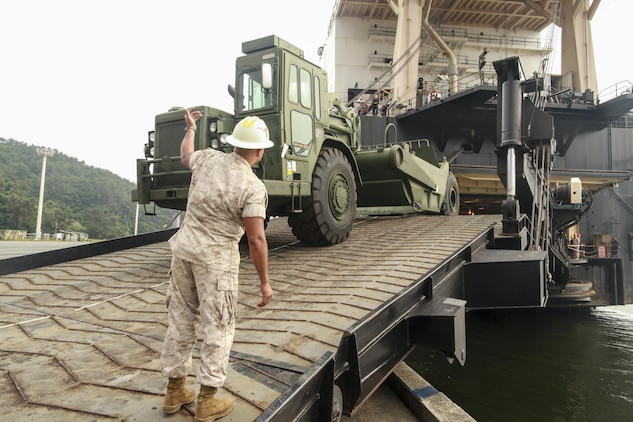 U.S. Marine Corps Gunnery Sergeant Sergio D. Barrios, the Offload Preparation Party (OPP) SNCOIC aboard the USNS 2nd Lt. John P. Bobo, III Marine Expeditionary Force, ground guides a 120-M grader during the MPF Offload of gear and equipment from the Bobo in Chinhae, South Korea, June 13, 2015 in support of Peninsula Express 15. Peninsula Express is one in a series of regularly-scheduled combined, small-unit, tactical training exercises that demonstrates continued dedication to the ROK-U.S. relationship, contributing to the security and stability of the Korean Peninsula and Asia-Pacific region. (U.S. Marine Corps photo by Sgt. Justin A. Bopp/Released)