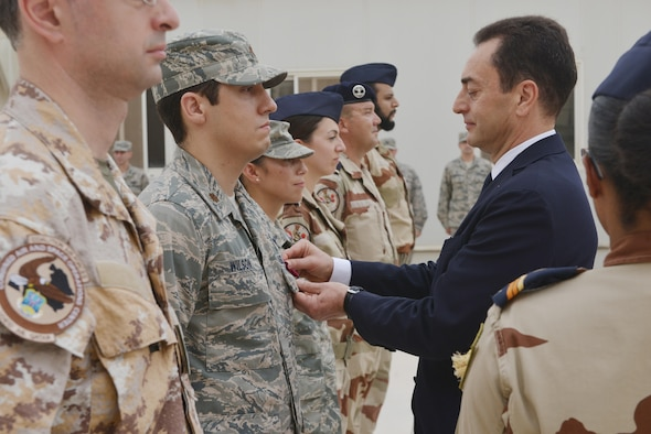 Monsieur Chevallier, Ambassador de France au Qatar, pins a French National Defense Medal onto U.S. Air Force Major Wilson, Combined Air Operation Center, during the Bastille Day ceremony July 14, 2015 at Al Udeid Air Base, Qatar. (U.S. Air Force photo/Staff Sgt. Alexandre Montes)
