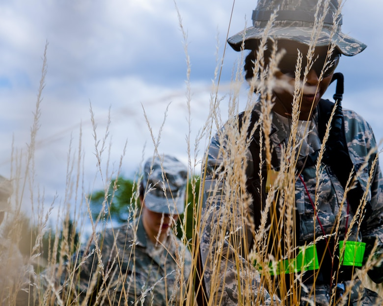 Medics from the 446th Aeromedical Staging Squadron make their way through the woods for the Care Under Fire exercise at Joint Base Lewis-McChord, July 12, 2015. The Care Under Fire exercise was designed locally by the 446th ASTS in order to simulate combat conditions and establish team oriented training scenarios. Medics were offered land navigation training in order to enhance their combat readiness in austere locations. (U.S. Air Force photo by Senior Airman Daniel Liddicoet/Released)