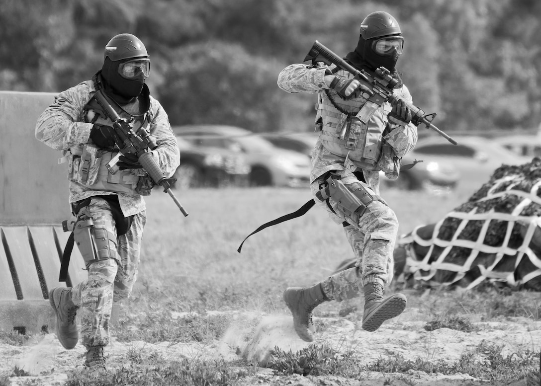 Two Airmen from the 96th Security Forces Squadron Airman run for cover during a shoot, move and communicate drill at Eglin Air Force Base, Fla, June 23, 2015. The mandatory training requirement is in addition to annual weapons qualification training. The exercise consists of Airmen firing simmunition ammo while advancing toward, away from and to the side of a target. This is followed by a building sweep and clear drill. The Defenders perform the highly kinetic training at Eglin's Base Tango range. The range was previously used for security forces pre-deployment training. (U.S. Air Force photo/Samuel King Jr.)