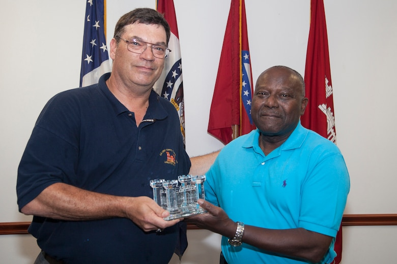 Dean Erickson, Little Rock District's Chief of Logistics, presents a crystal Corps Castle to Henry Hollins in appreciation for his service and dedication to duty.  Hollins served as the District's facility manager for more than 20 years.