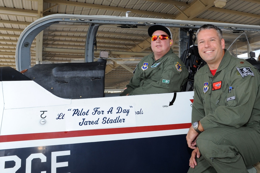 """Jared Stadler,Cole High School student, sits in the cockpit of a T-6 Texan II while Maj. Todd Salzweder, 560th Flying Training Squadron director of staff, explains the aircraft controls July 17, 2015, during a Pilot for a Day event at Joint Base San Antonio-Randolph. Since 1994, squadron members have sponsored the """"Pilot for A Day"""" program for children of all ages with chronic illnesses.   The goal of the program is to give these children a break from the challenges they face each day because of their illnesses. (U.S. Air Force photo by Melissa Peterson/Released)"""