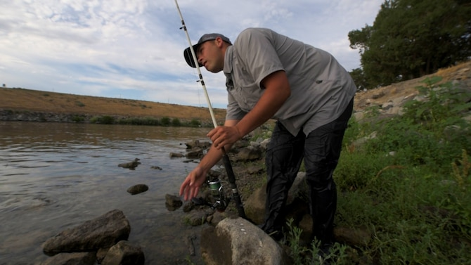 Senior Airman Jaye Legate, 366th Fighter Wing Public Affairs broadcast journalist, sets the drag on his fishing pole July 6, 2015, at Crane Falls, Idaho. Legate was hoping to land a White Sturgeon, one of the more elusive fish in the region. (U.S. Air Force photo by Airman 1st Class Connor J. Marth)