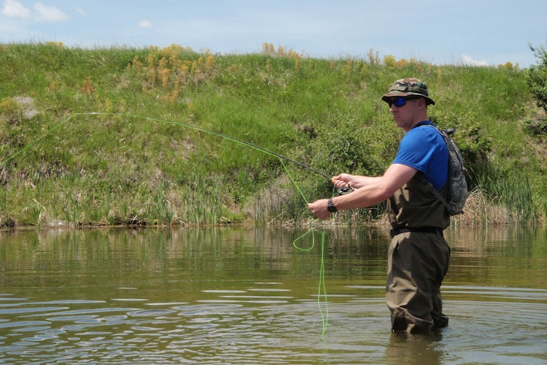 Tech. Sgt. Chad Thompson, 341st Missile Wing Public Affairs, hooks a fish during a recent fishing outing to Pelican Point, June 7, 2015. Thompson has fallen in love with the outdoors since arriving to Montana and fly fishing is just one way he relieves his stress. (Courtesy photo)