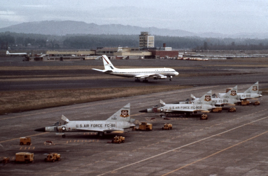A row of F-102 Delta Daggers assigned to the 337th Fighter Group stand ready at the Portland Air Force Base, Ore., as a commercial aircraft taxis along a shared runway at the Portland International Airport. The photograph was taken in the early 1960's when the 337th shared the alert mission with the 142nd Fighter Group prior to the official transfer of the aircraft and full time alert mission to the 142nd on April 1, 1966. (photo courtesy of the 142nd Fighter Wing History Office)