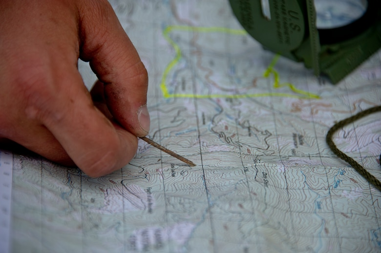 Airman 1st Class Zachary Mikolajczyk, 22nd Training Squadron Survival, Evasion, Resistance and Escape specialist, points at a location on a field training area map June 13, 2015, in the Colville National Forest, Wash. Mikolajczyk showed the S-V-80-A combat survival students how to find their location on a map. The students learned a variety of skills to include fire crafts, water procurement, land navigation and shelter building. (U.S. Air Force photo/Airman 1st Class Nicolo J. Daniello)