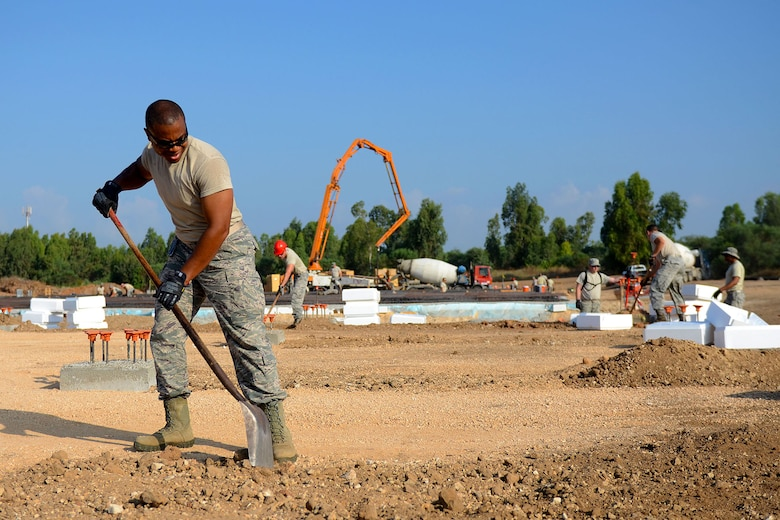 U.S. Air Force Staff Sgt. Dontavious Cooper, a heating, ventilation and air-conditioning technician with the South Carolina Air National Guard's 169th Civil Engineer Squadron at McEntire Joint National Guard Base, S.C., levels ground to lay foundations for multi-purpose buildings being constructed in support of a Deployment for Training in Israel, June 29, 2015. The construction project is to help S.C. PRIME BEEF Airmen maintain their civil engineering specialties. Swamp Fox civil engineers are working alongside 200th RED HORSE Squadron and U.S. Navy SEABEES civil engineers during the training exercise. (South Carolina Air National Guard photo by Tech. Sgt. Caycee R. Watson / RELEASED)