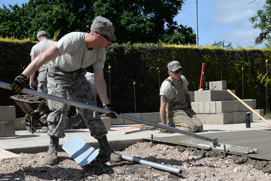 U.S. Air Force Airman 1st Class Gregory Myers, left, 100th Civil Engineer Squadron Pavements and Equipment journeyman from Bakersfield, Calif., uses a bull float to remove any imperfections while leveling concrete June 18, 2015, on RAF Mildenhall, England. The bull float pushes any of the larger aggregate down and brings any of the residual water to the surface. (U.S. Air Force photo by Gina Randall/Released)
