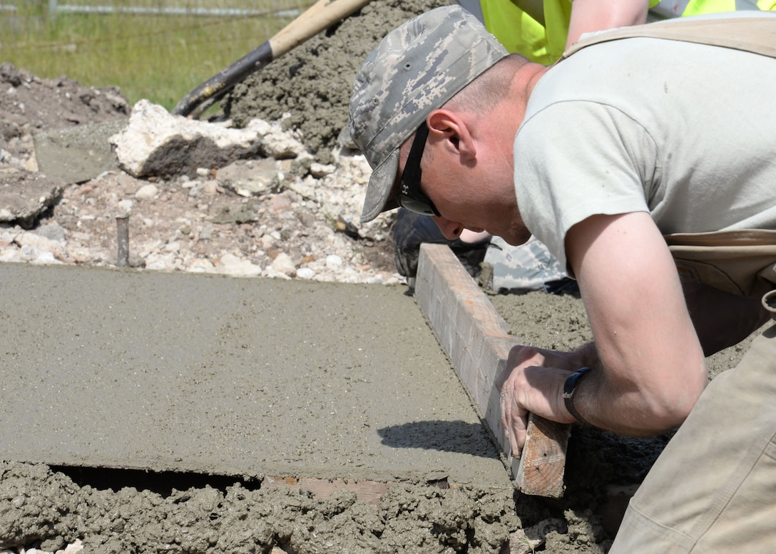 U.S. Air Force Senior Airman Stephen Beasley, 100th Civil Engineer Squadron Pavements and Equipment journeyman from Wakeforest, N.C., removes any excess concrete from a path being laid June 18, 2015, on RAF Mildenhall, England. The wooden screed board was used by two Airmen working together sliding the board back and forth along the two preplaced forms that are used to hold the concrete in place while it dries. (U.S. Air Force photo by Gina Randall/Released)