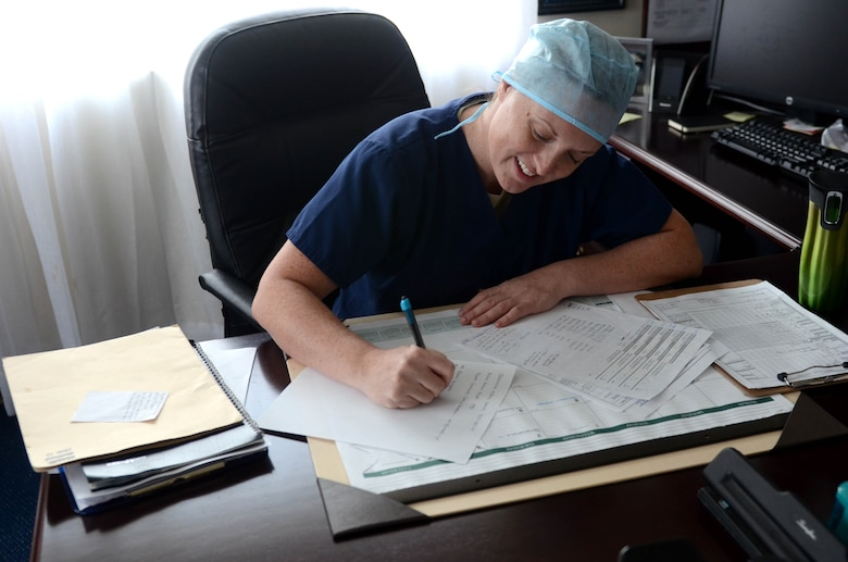 U.S. Army Capt. Dr. Annie Eure, Andersen Air Force Base Veterinary Services Branch chief, completes paperwork after a long day of work July 9, 2015 at Andersen AFB, Guam. The Andersen AFB Veterinary Treatment Facility provides care for more than 2,000 active animal patients. (U.S. Air Force photo by Airman 1st Class Alexa Ann Henderson/Released)