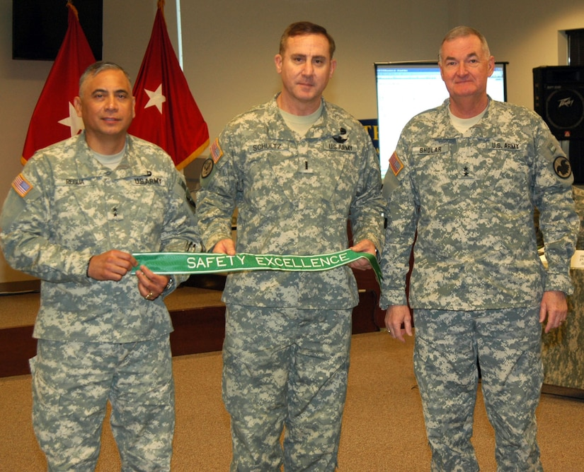 The 75th Division Commander Maj. Gen Eldon Regua and Division Safety Officer Chief Warrant Officer Robert Shultz, accepts the Army Safety Excellence Streamer from Maj. Gen. James Sholar, Deputy Commanding General, United States Army Reserve Command.  The 75th Division earned the award by achieving 12 consecutive months without a Soldier or unit at fault Class A or B accident.