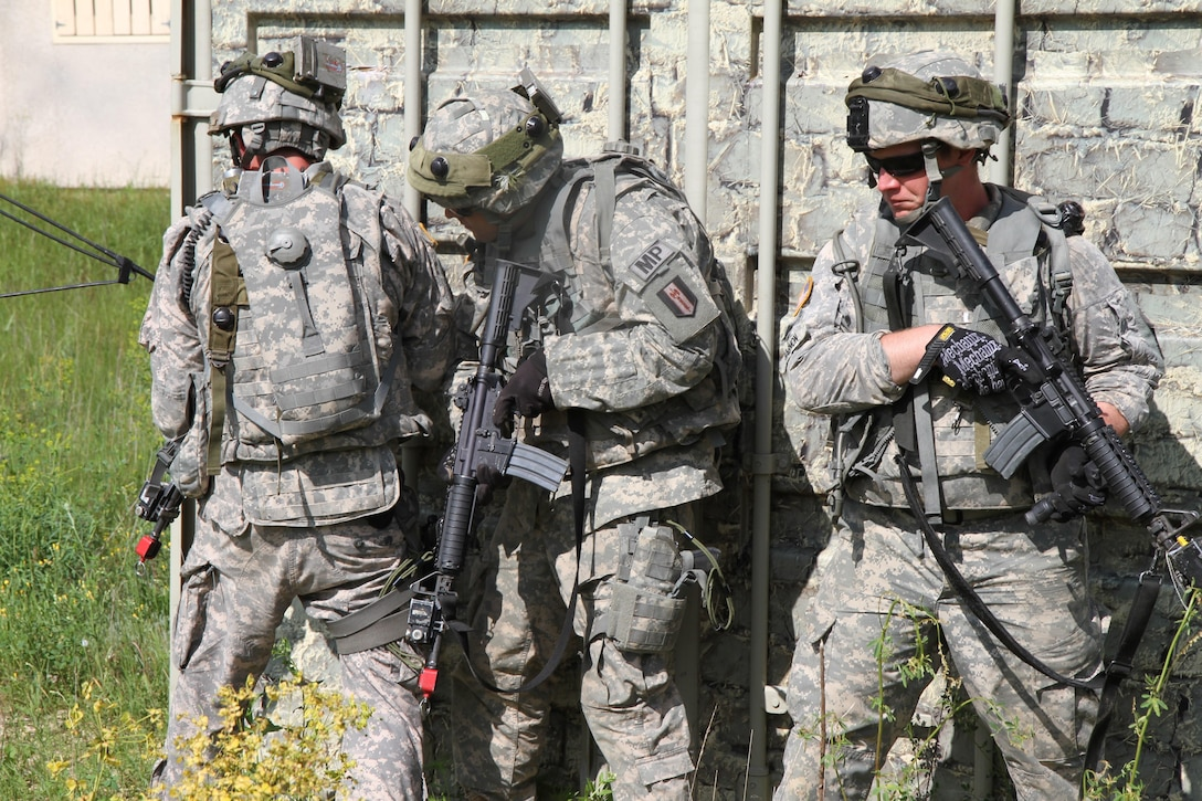 U.S. Army Soldiers assigned to the 94th Military Police Company use improvised cover during training at a Military Operation on Urbanized Terrain site at Fort McCoy, Wis., June 14, 2015. Soldiers of the 94th MP Company conducted training to improve unit readiness during Combat Support Training Exercise 78-15-02. The 78th Training Division's Combat Support Training Exercise is a multi-component and joint endeavor which is integrated with Global Medic and QLLEX and occurring simultaneously at seven installations nationwide.