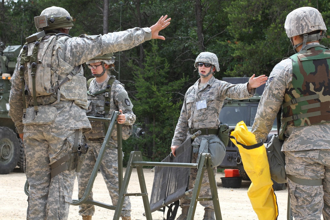 U.S. Army Soldiers assigned to the 46th Chemical Company speak with Senior Airman Derek R. Aalerud, assigned to the 439th Civil Engineering Squadron, to establish hot and cold lines within the contamination control area during a simulated chemical decontamination training exercise at Tactical Training Base Patriot on Fort McCoy, Wis., June 18, 2015. Soldiers and Airmen worked together to improve mission readiness as part of Combat Support Training Exercise (CSTX) 78-15-02. The 78th Training Division's CSTX is a multi-component and joint endeavor which is integrated with Global Medic and QLLEX and occurring simultaneously at seven installations nationwide.