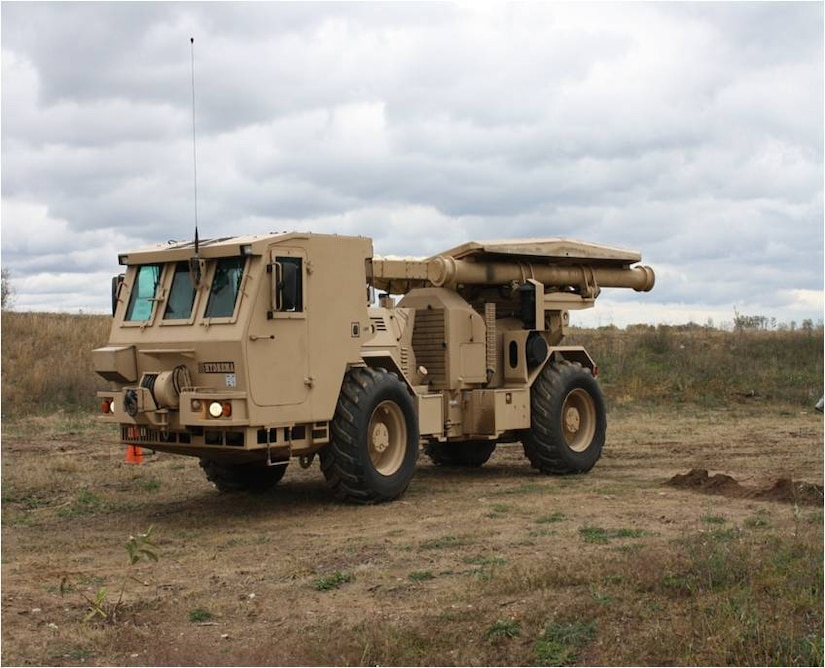 An M1271 Medium Flail Mine Clearing Vehicle is equipped with a rotating flail and 72 chains with fist-sized balls, or hammers, at the end of the chains. As the vehicle drives backwards over the designated area, the flail rotates and the chains dig into the ground tearing mines apart or detonating them. The driver is protected by a deflector shield of armored steel, protecting the both the driver and vehicle against blast pressure and mine fragments.