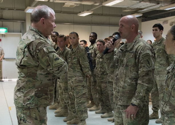 U.S. Army Gen. Martin E. Dempsey, chairman of the Joint Chiefs of Staff, takes a question from a service member deployed to Iraq during a town hall in Baghdad, July 18, 2015.