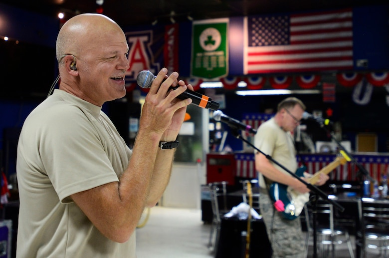 Staff Sgt. Darran Keenom, a U.S. Air Forces Central Command band vocalist, guitarist and harmonica player, sings during a performance at an undisclosed location in Southwest Asia July 6, 2015. The band is composed of musicians who perform and tour throughout the area of responsibility to encourage troop morale, diplomacy and outreach to host nation communities. (U.S. Air Force photo/Senior Airman Racheal E. Watson)
