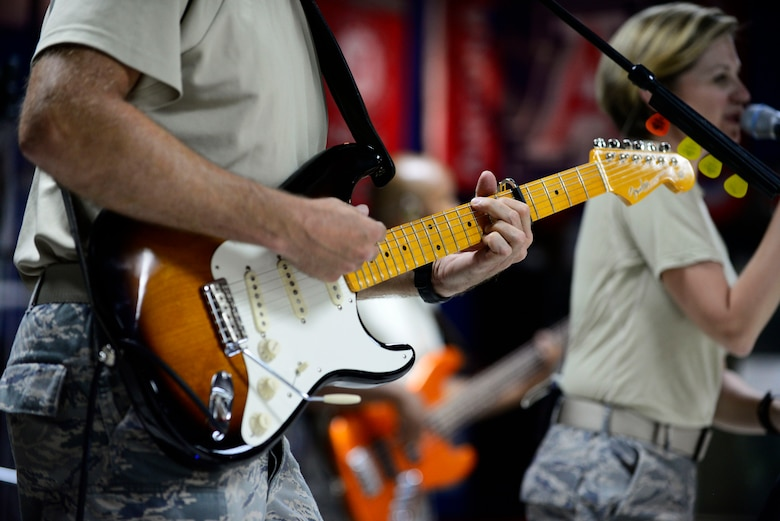 Staff Sgt. Darran Keenom, a U.S. Air Forces Central Command band vocalist, guitarist and harmonica player, strums a guitar during a performance at an undisclosed location in Southwest Asia July 6, 2015. The band played several genres of music to appeal to all ages. (U.S. Air Force photo/Senior Airman Racheal E. Watson)
