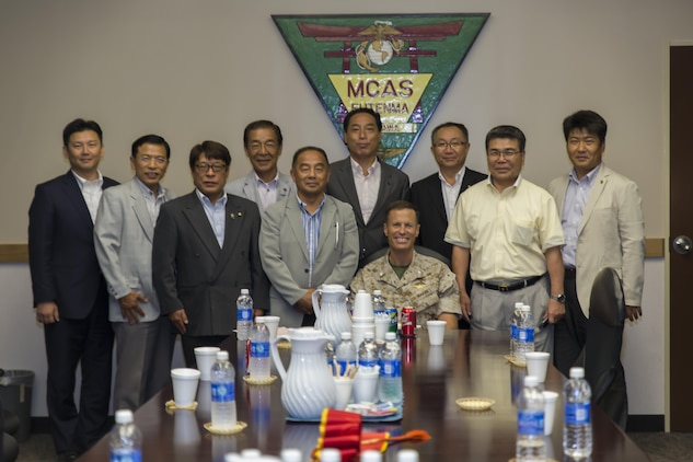 Lt. Col. James Hurd, executive officer for Marine Corps Air Station Futenma, Japan, poses for a group photo with Toshiyuki Kuwabara, center, chairman of the Iwakuni City Council, and other members of the council during a visit to the station to conduct a study tour, July 16, 2015. Chugoku Shikoku Defense Bureau officials, Okinawa Defense Bureau officials and Ginowan City Council members also visited MCAS Futenma to help deepen the their understanding on national security here, and the mission of MCAS Futenma in support of III Marine Expeditionary Force's aviation warfighting capabilities.